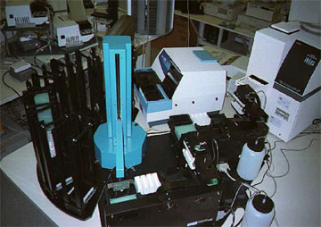 Bench layout of PlateCrane XL, dual Precision 2000 pipetting systems, and three interchangeable detectors.