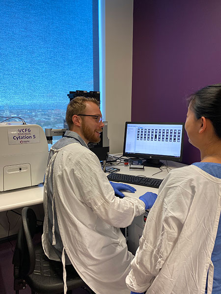 Researchers Robert Vary (left) and Jennii Luu (right) reviewing Cytation 5 generated data at the VCFG facility.